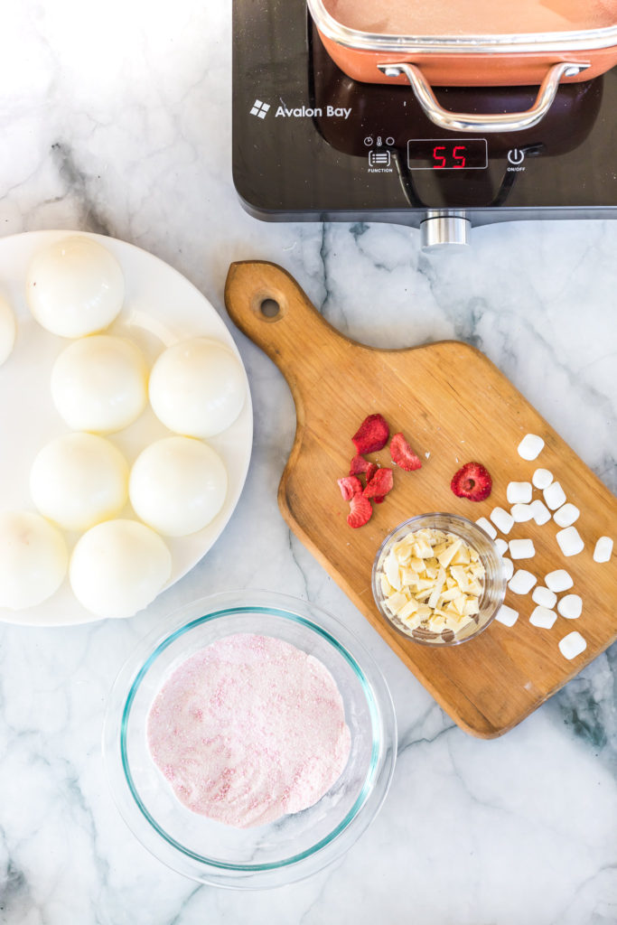 white chocolate strawberry hot cocoa bombs with ingredients on cutting board on a marble counter